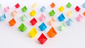 Flotta av origamipappersskepp i triangelform som isoleras på vit royaltyfri foto