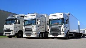 Flotte de camions blancs de Scania et de Volvo sur une cour Images libres de droits