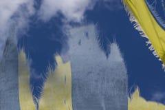 Flottement dans le tissu bleu et jaune de vent dans le ciel Image libre de droits