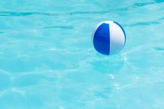 Flottement du beachball bleu et blanc dans la piscine photo libre de droits