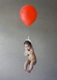 Flotteur de bébé avec un ballon rouge Photos libres de droits