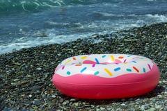 Flotteur de beignet arrosé par hippie dans des vagues de mer Fond d'été photos libres de droits