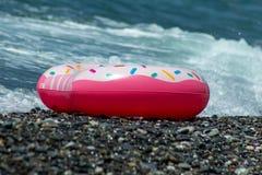 Flotteur de beignet arrosé par hippie dans des vagues de mer Fond d'été photo stock