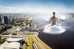 Flotteur de femme au-dessus de ville Photos stock