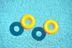 Flotteur jaune de piscine, anneau de piscine dans le bleu frais régénérant la piscine bleue Photographie stock libre de droits