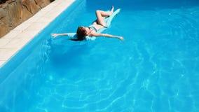 Flotteur millénaire de fille à la piscine, festival, hôtel, plage, événement souriant avec des lunettes de soleil dessus pendant  clips vidéos