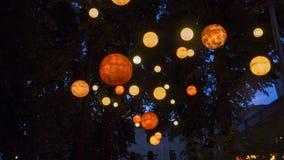 Flotteur rougeoyant orange de globes en ciel nocturne Image stock