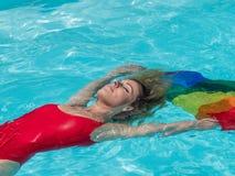 Flotteurs blonds caucasiens de fille dans la piscine avec le drapeau de la fierté photographie stock libre de droits