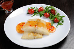 Flounder fillets in sauce with arugula and cherry tomatoes Royalty Free Stock Images