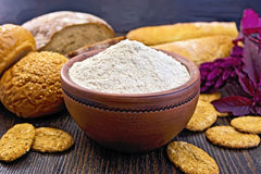 Flour amaranth in clay bowl with bread on board. Amaranth flour in a clay bowl with bread and biscuits, purple amaranth flower on the background of wooden boards Royalty Free Stock Photography