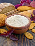 Flour amaranth in clay bowl with cookies on board Royalty Free Stock Image
