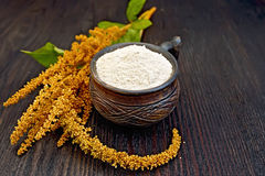 Flour amaranth in clay cup on dark board Royalty Free Stock Images