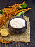 Flour amaranth in clay cup with flower on sackcloth. Flour amaranth in a clay cup, a spoon with grain, brown flower with leaves on a napkin from a sacking on a Royalty Free Stock Photography