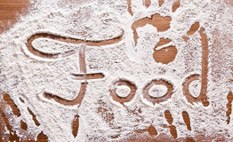 Flour Artwork With Food And Handprints. Fun background with the word FOOD and human handpints in scattered flour on a wooden tabletop Royalty Free Stock Images