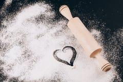 Flour avec le coeur et la goupille sur le noir Photographie stock libre de droits