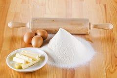 Flour avec les oeufs, la goupille et le beurre photographie stock libre de droits