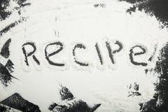 Flour on a black table, an inscription recipe.  stock photo