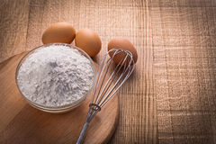 Flour in bowl corolla eggs on wooden board food Royalty Free Stock Photos