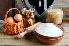 Flour in a bowl and eggs in basket Royalty Free Stock Image