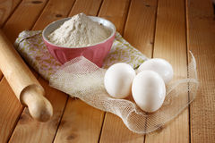 Flour in bowl with eggs and rolling pin over wood table Royalty Free Stock Image