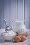 Flour in bowl scoop egs corolla jug with milk on Royalty Free Stock Image