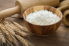 Flour in bowl and wheat on wooden table Royalty Free Stock Image