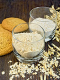 Flour and bran oat in glass with cookies on board Royalty Free Stock Photo