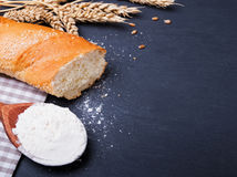 Flour, bread and wheat ears on black background Royalty Free Stock Photos