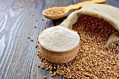 Flour buckwheat in bowl and spoon with cereals on board Royalty Free Stock Photography