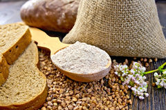 Flour buckwheat in spoon with cereals and bread on board Royalty Free Stock Photo