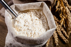Flour in burlap sack with scoop of metal Royalty Free Stock Photos