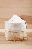 Flour in a canvas bag and ear of wheat on the wooden. Stock Photography