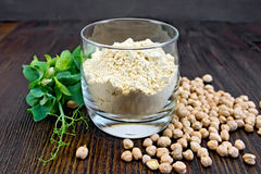 Flour chickpeas in glassful with peas on board Stock Photography