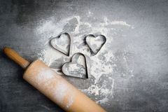 Flour, cookie cutters shaped as heart and rolling pin on a stone Stock Photography