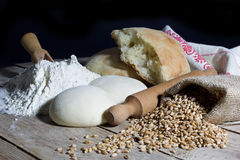 Flour, Dough, Bread, Rolling Pin and Jute Bag Filled with Wheat on Wooden Table Over Black Background Stock Photos