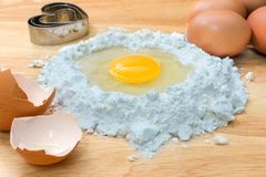 Flour with egg and ingredients for homemade bakery on wooden background.  Stock Photography