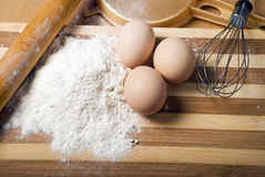 Flour and eggs. On a wooden board Stock Image