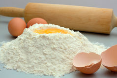 Flour and eggs on a kitchen table. For preparation a dough Royalty Free Stock Photos