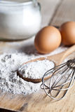 Flour, eggs and kitchen utensil Stock Image