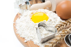 Flour, eggs, rolling pin and baking forms on wooden board Stock Photography