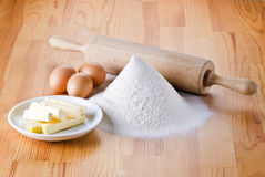 Flour with eggs, rolling pin and butter Stock Photo