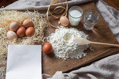 Flour, eggs and sheet of recipe on a wooden board Royalty Free Stock Image