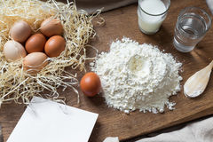 Flour, eggs and sheet of recipe on a wooden board Stock Photos