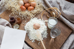 Flour, eggs and sheet of recipe on a wooden board Stock Photography