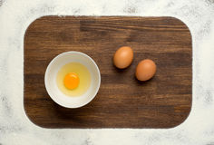 Flour and eggs on a wooden board Royalty Free Stock Photography