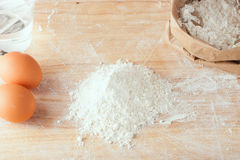 Flour and eggs on wooden board Stock Images
