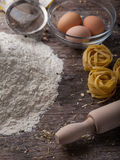 Flour and eggs on a wooden kitchen table Stock Photos
