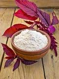 Flour el amaranto en cuenco de la arcilla a bordo con la flor púrpura Fotos de archivo