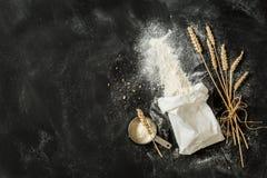 Flour el bolso, los oídos del trigo y la taza de medición en negro Fotografía de archivo