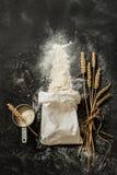 Flour el bolso, los oídos del trigo y la taza de medición en negro Fotos de archivo